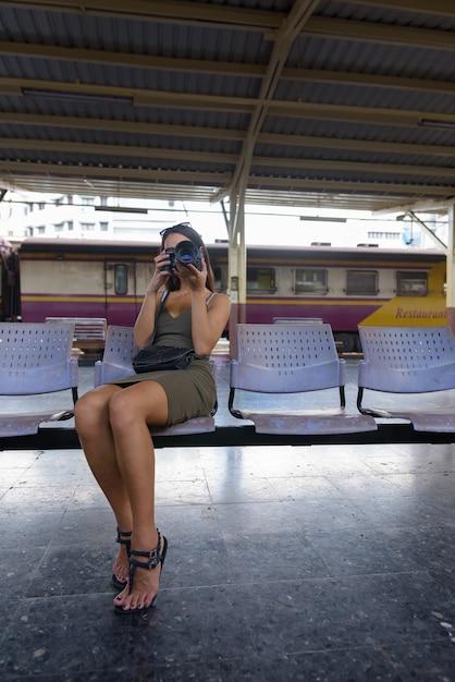 Junge touristenfrau, die sitzt und mit kamera fotografiert Premium Fotos