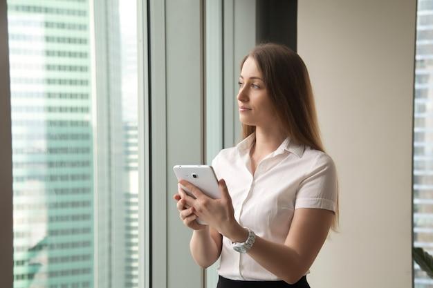 Junge träumerische schöne geschäftsfrau, die durch fenster beim halten der tablette schaut Kostenlose Fotos