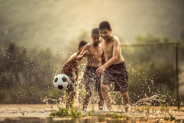 Junge tritt einen fußball (fokus auf fußball) Premium Fotos