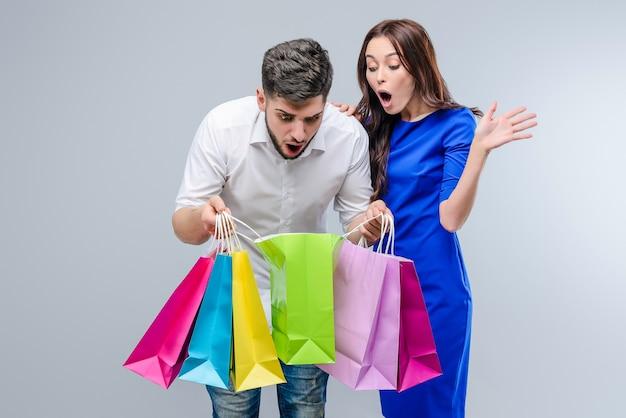 Junge überraschte leute schauen innerhalb der einkaufstaschen, die über grau lokalisiert werden Premium Fotos