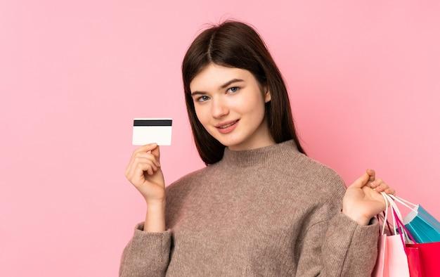 Junge ukrainische jugendlichfrau über der lokalisierten rosa wand, die einkaufstaschen und eine kreditkarte hält Premium Fotos