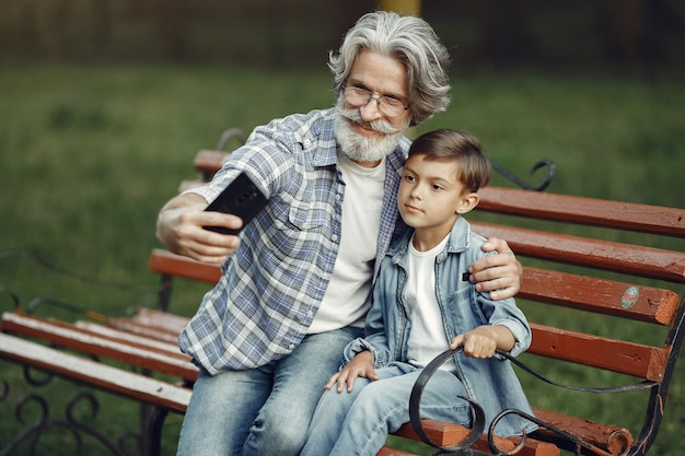 Junge und großvater sitzen auf einer bank. familie im park. alter mann, der mit enkel spielt. großvater benutzt ein telefon. Kostenlose Fotos