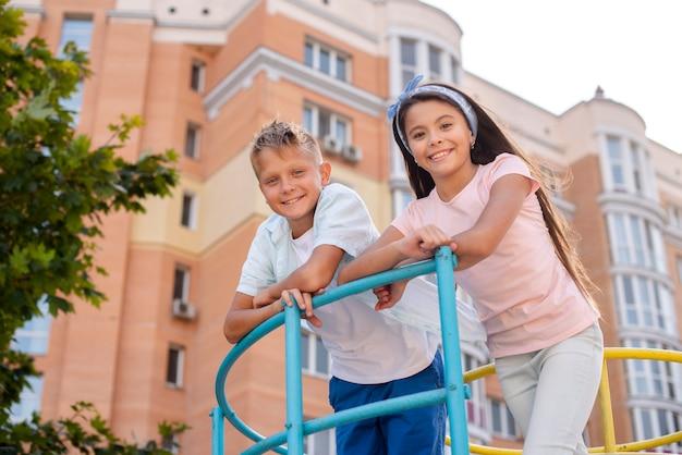 Junge und mädchen, die auf einer metallstange sich lehnen Kostenlose Fotos