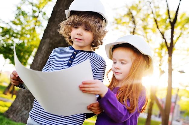 Junge und mädchen in den bausturzhelmen, die weißes blatt papier betrachten oder zeichnen und lächeln Premium Fotos