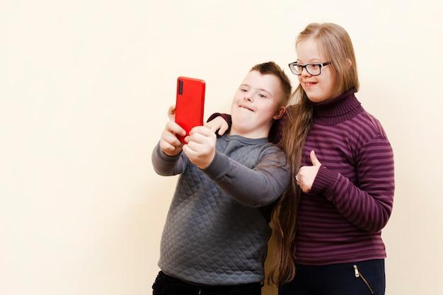 Junge und mädchen mit down-syndrom machen ein selfie Premium Fotos