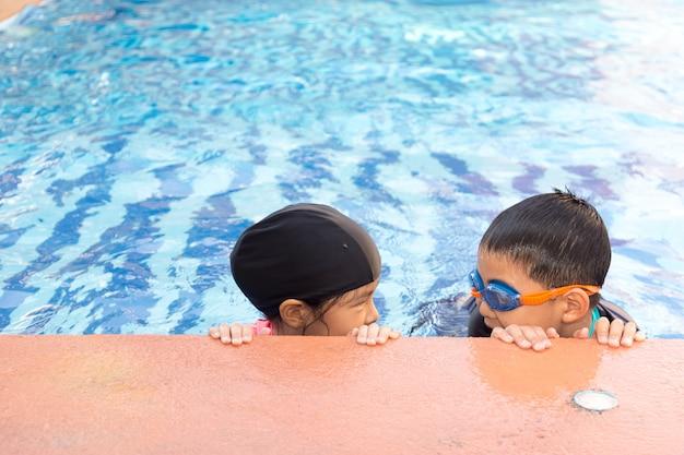 Junge und mädchen schwimmen im pool. Premium Fotos
