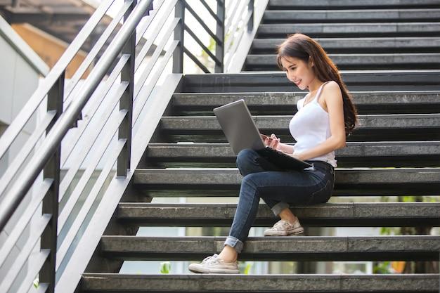 Junge und schöne asiatische frau, die mit ihrem laptop beim sitzen auf den jobstepps arbeitet Premium Fotos