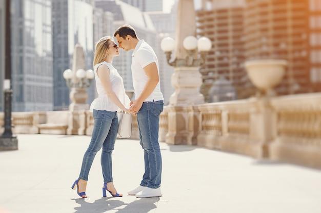 Junge und stilvolle liebhaber verbinden in den weißen t-shirts und in den blue jeans, die in eine große stadt gehen Kostenlose Fotos