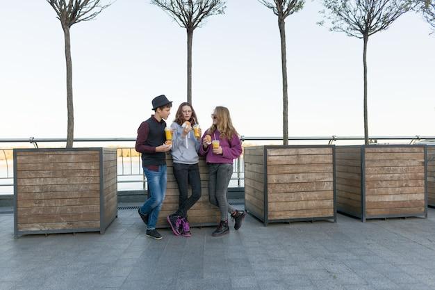 Junge und zwei mädchen auf stadtstraße mit burgern und orangensaft Premium Fotos