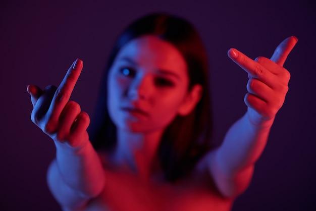 Junge unhöfliche frau zeigt ficken sie geste, während sie in der dunkelheit stehen und ihre hände halten Premium Fotos