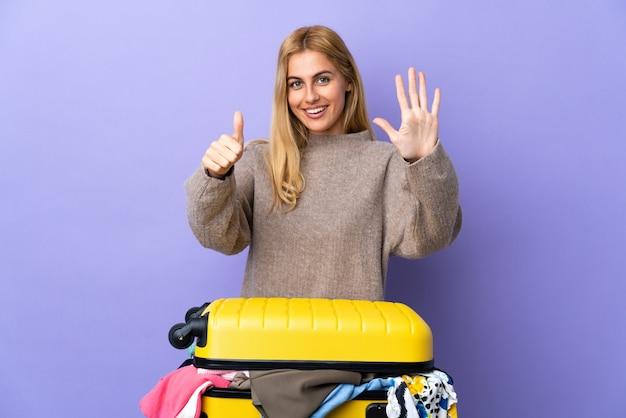 Junge uruguayische blonde frau mit einem koffer voller kleider über isolierter lila wand, die sechs mit den fingern zählt Premium Fotos