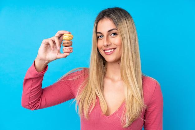 Junge uruguayische frau über isolierter blauer wand, die bunte französische macarons hält und viel lächelt Premium Fotos