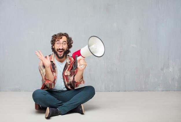 Junge verrückte verrückte dummkopfhaltung mit einem megaphon. Premium Fotos