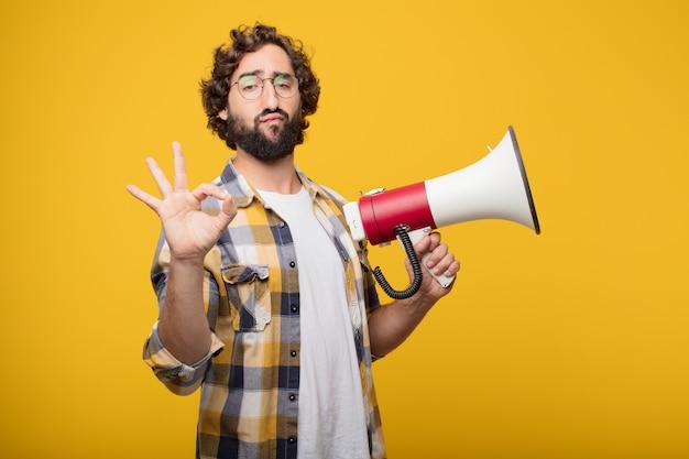 Junge verrückte verrückte manndummkopfhaltung mit einem megaphon. ankündigung co Premium Fotos