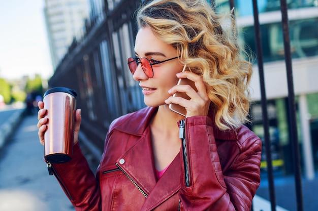 Junge verträumte blonde frau, die in der stadt geht und smartphone verwendet. nahaufnahme details. stilvolles modernes mädchen mit kaffee. windige haare. Kostenlose Fotos