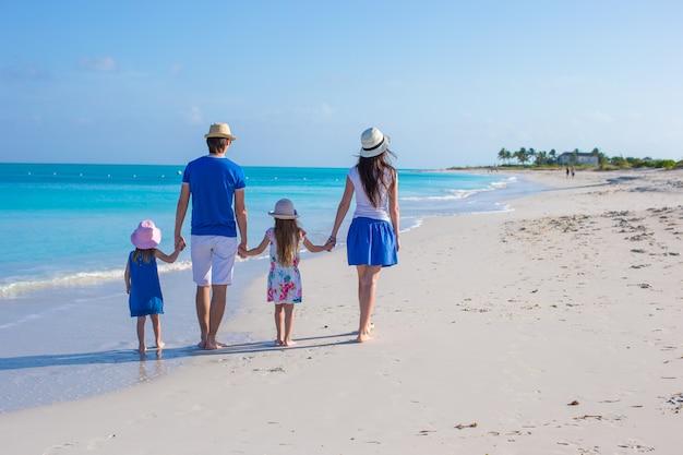 Junge vierköpfige familie der hinteren ansicht auf tropischem strand Premium Fotos