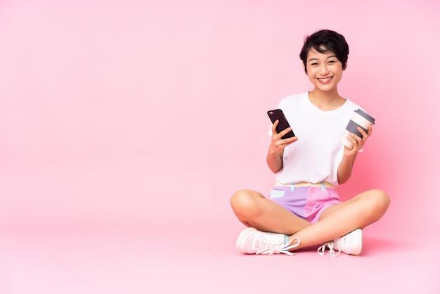 Junge vietnamesische frau mit den kurzen haaren, die auf dem boden über der isolierten rosa wand sitzen, die kaffee hält, um und ein handy wegzunehmen Premium Fotos