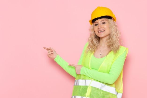 Junge weibliche baumeisterin der vorderansicht im gelben helm des grünen bauanzugs, der lächelt und auf dem konstruktionsfoto der rosa raumjobarchitektur hervorhebt Kostenlose Fotos