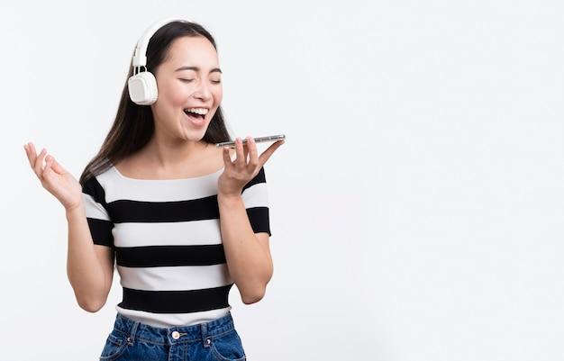 Junge weibliche hörende musik auf mobile Kostenlose Fotos
