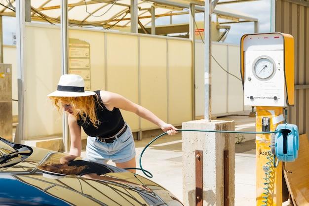 Junge weibliche pumpende autoreifen an der tankstelle Kostenlose Fotos