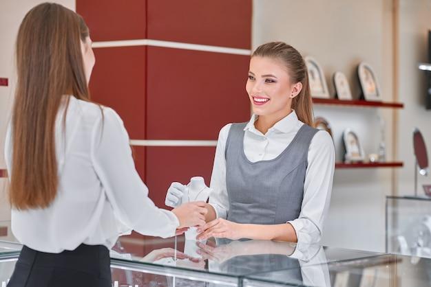 Junge weibliche schmuckarbeiterin, die hilft, eine halskette für eine frau in einem juweliergeschäft zu wählen Premium Fotos