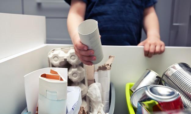 Junge wirft papiermüll in einen von vier verschiedenen behältern, um müll zu sortieren. Premium Fotos