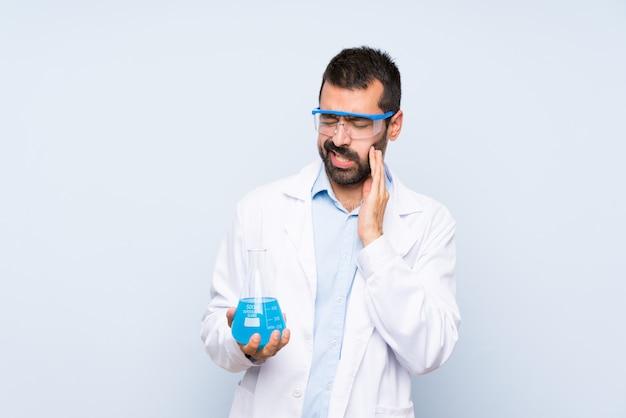 Junge wissenschaftliche haltene laborflasche über lokalisiertem hintergrund mit zahnschmerzen Premium Fotos