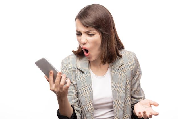 Junge wütende geschäftsfrau, die nachricht im smartphone betrachtet und ihre wut ausdrückt Premium Fotos