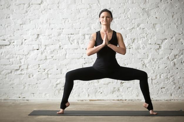 Junge yogi attraktive frau in göttin pose, weiße loft backgrou Kostenlose Fotos