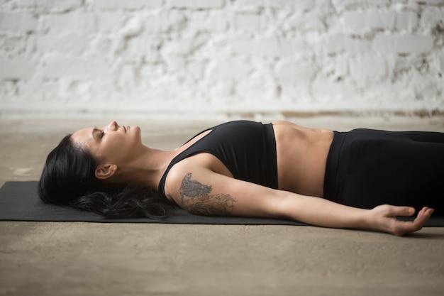 Junge yogi attraktive frau in savasana pose, loft hintergrund, c Kostenlose Fotos