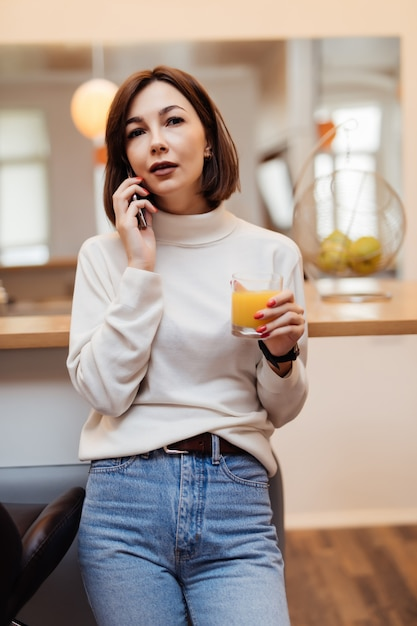 Junge zarte dame im weißen t-shirt und in den blauen jeans in der küche, die am telefon sprechen Kostenlose Fotos