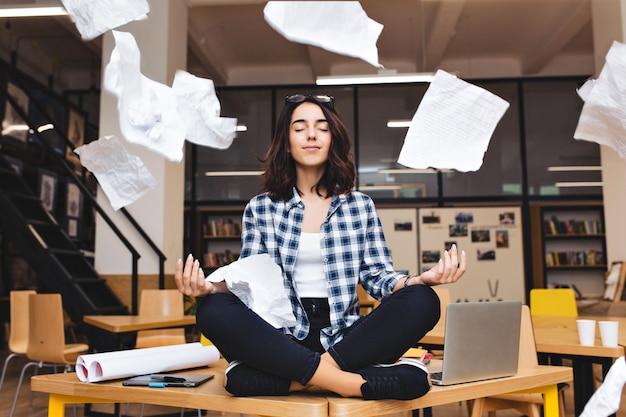 Junge ziemlich freudige brünette frau, die über tischumrandungsarbeitszeug und fliegende papiere meditiert. fröhliche stimmung, pause machen, arbeiten, lernen, entspannen, wahre emotionen. Kostenlose Fotos