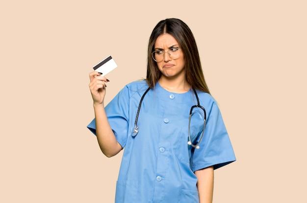 Jungekrankenschwester, die eine kreditkarte auf lokalisiertem gelbem hintergrund hält Premium Fotos