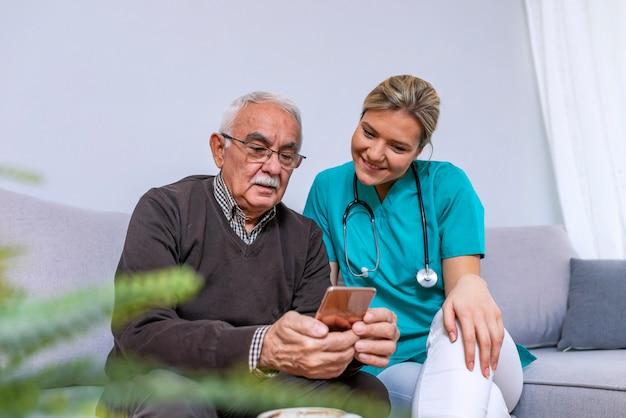 Jungekrankenschwester, die zeit mit glücklichem älterem patienten im pflegeheim verbringt Premium Fotos