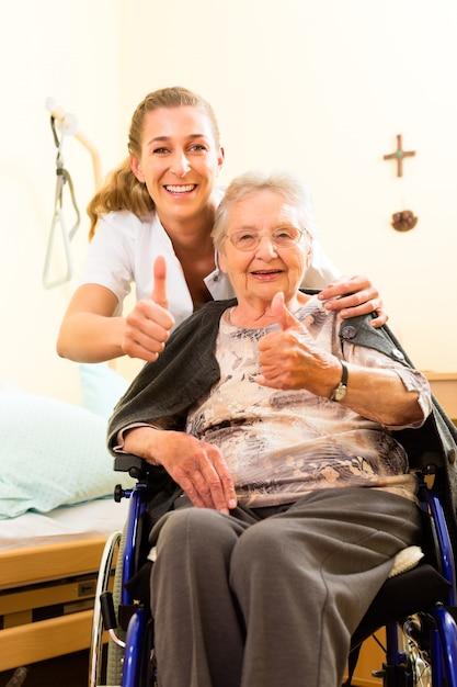 Jungekrankenschwester und weiblicher senior im pflegeheim Premium Fotos