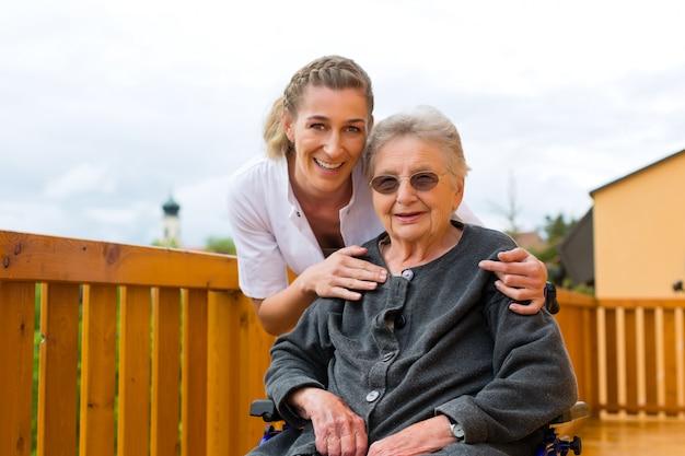 Jungekrankenschwester und weiblicher senior in einem rollstuhl Premium Fotos