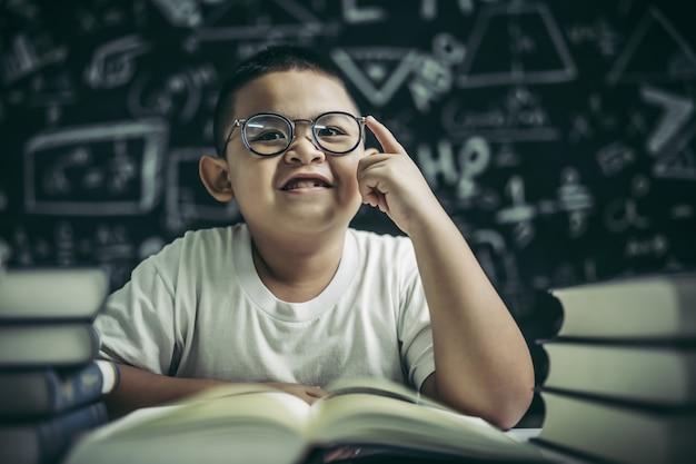 Jungen mit brille schreiben bücher und denken im klassenzimmer Kostenlose Fotos