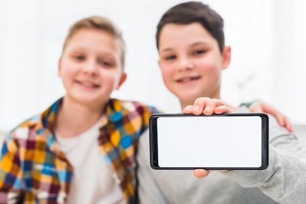 Jungen präsentieren smartphone-vorlage Kostenlose Fotos