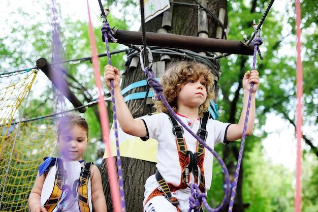 Jungen und mädchen im seilpark passieren hindernisse. Premium Fotos