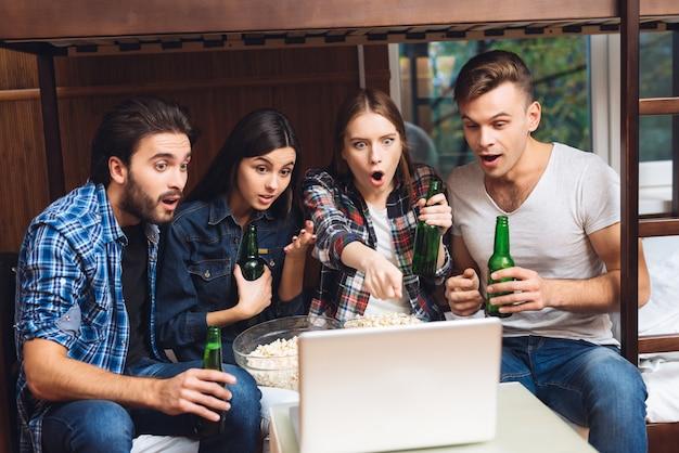 Jungen und mädchen schauen sich einen film auf einem laptop mit bier an. Premium Fotos