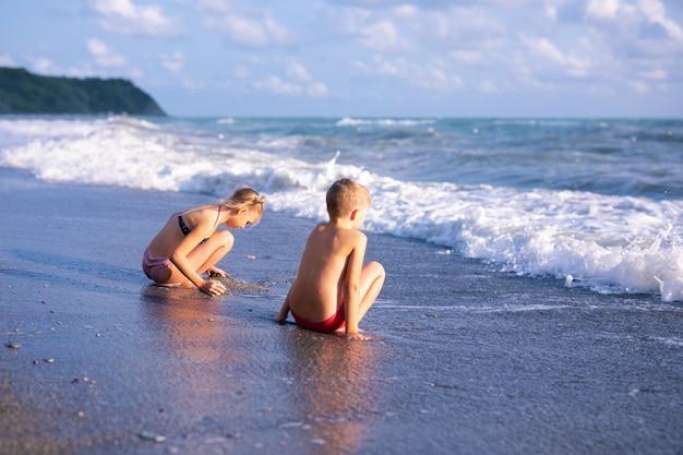 Jungen und mädchen spielen am strand in den sommerferien. kinder in der natur mit schönem meer, sand und blauem himmel. Premium Fotos
