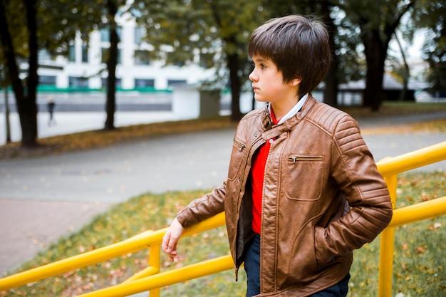 Jungenjugendlichstand auf den schritten im park Premium Fotos