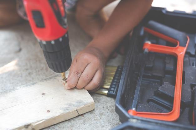 Jungenkind, das elektroschrauber der handwerkzeuge hält. Kostenlose Fotos