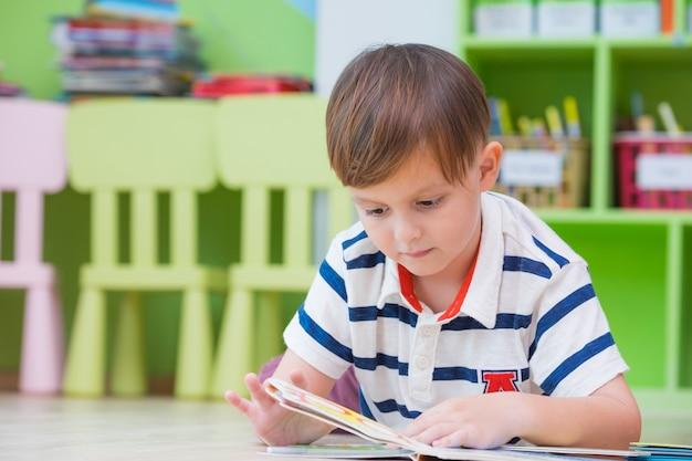 Jungenkind legte sich auf boden nieder und las geschichtenbuch Premium Fotos