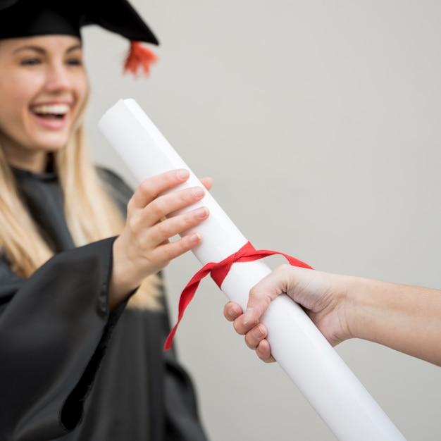 Junger absolvent, der ihr zertifikat erhält Kostenlose Fotos