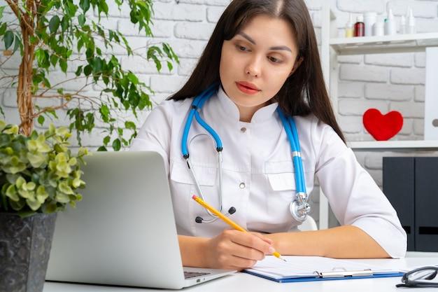 Junger ärztinkardiologe, der an ihrem schreibtisch und an arbeiten sitzt Premium Fotos