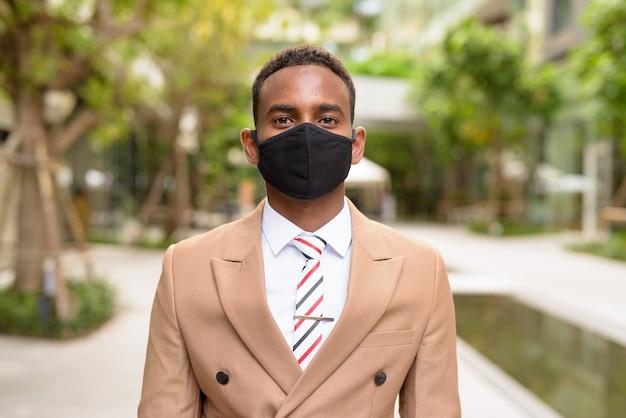 Junger afrikanischer geschäftsmann, der maske zum schutz vor coronavirus-ausbruch in der stadt mit natur trägt Premium Fotos