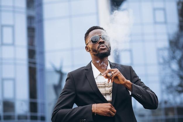 Junger afrikanischer geschäftsmann in rauchender zigarette der noblen klage Kostenlose Fotos