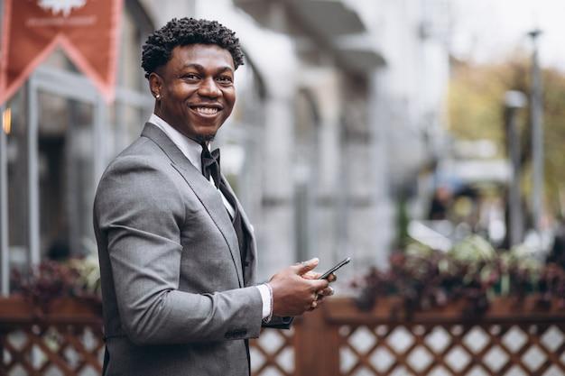 Junger afrikanischer geschäftsmann unter verwendung des telefons Kostenlose Fotos