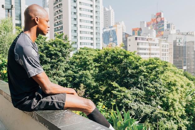 Junger afrikanischer männlicher athlet, der am rand der dachspitze die stadt übersehend sitzt Kostenlose Fotos